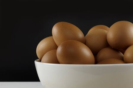 Close up fresh chicken eggs on linen tablecloth and white table with copy space . Standard-Bild