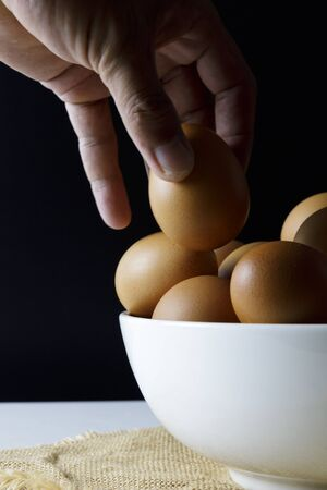 Close up fresh chicken eggs on linen tablecloth and white table with copy space .Hand man hold chicken egg.
