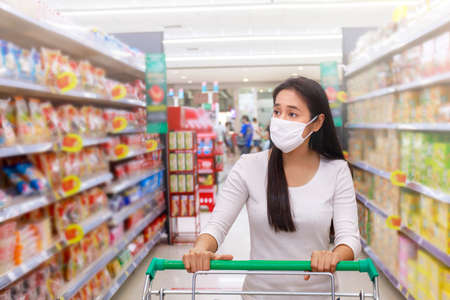 Asian woman wear face mask push shopping cart in supermarket department store. Girl looking grocery to buy something. During coronavirus crisis or covid19 outbreak. Women wearing protective face mask