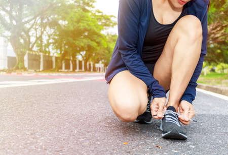 Close up of young woman runner tying laces her shoelaces.  Hands asian women tying her black shoe.  Woman wear running shoe on to walking park. Healthy and fitness concept. With copy space.
