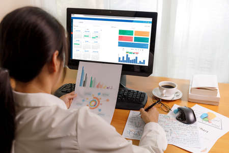 Rear view of businesswoman working in office with computer holding chart report paper and looking. businesswoman analysis scheduler data on PC screen. Business people check calendar planner organization on PC. Business and finance concept.