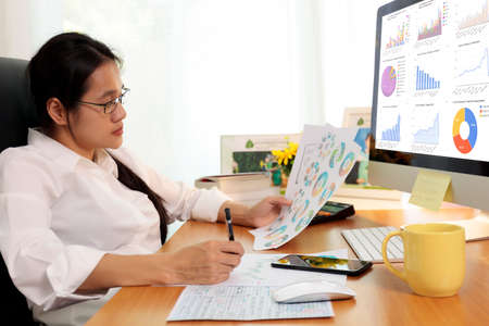 Business woman working in office with computer holding chart report paper and looking. business people working at home with paper and PC screen. Business and finance ,work at home concept