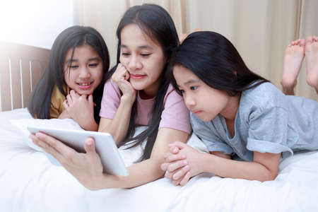 Happy Asian family enjoy and relax on bed in bedroom. mother and daughters enjoy using tablet together on bed. Family concept. Foto de archivo