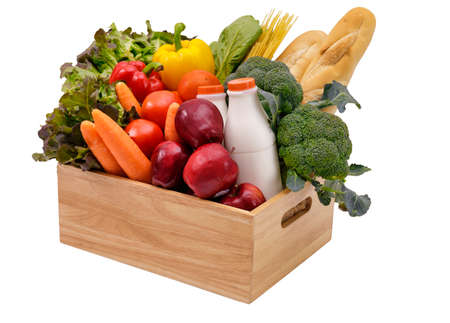 Wooden crate with multi color vegetables , fruit, milk and baguette isolated on white background. Grocery in wood crate . Stockfoto