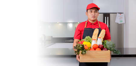 Grocery delivery courier man in red uniform and apron with grocery box with food, fresh fruit and vegetable. Deliver man handling wooden crate of food, fruit, vegetable