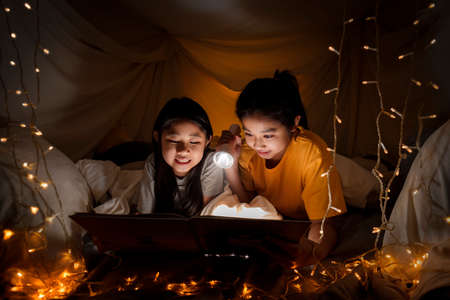 Family concept. elder sister and sister reading book with flashlight together before bedtime. Sister read story book together in bed sheet tent. focus selective little sister. With film grain effect