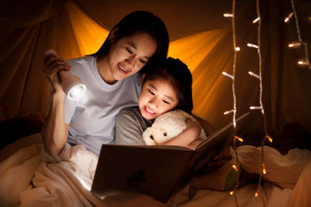 Family concept. Mother and child daughter reading book with flashlight together in children tent before bedtime. Happy mother read story book to her daughter in bed sheet tent Archivio Fotografico