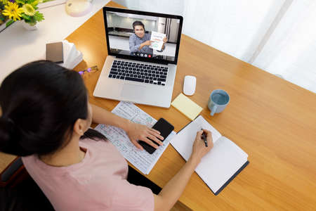 Business long distance video call, businessman and businesswoman analysis financial report using videoconference application for virtual communication, online meeting with videochat app. Covid-19 work from home.