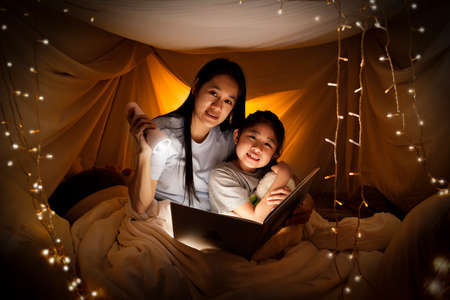 Family concept. Mother and child daughter reading book with flashlight together in children tent before bedtime. Happy mother read story book to her daughter in bed sheet tent 写真素材