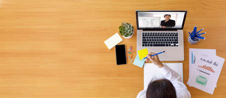 Top view Businessman and businesswoman analysis financial chart with videoconference online meeting. Business people using laptop meeting with diverse colleagues. Covid-19 working from home. Foto de archivo