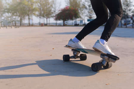Close-up and motion movement Asian women surf skate or skateboard outdoors on beautiful morning. Happy young women play surf skate at park on morning time. Close up Asian women leg wear sneaker paly surf skate on public park. Sport concept