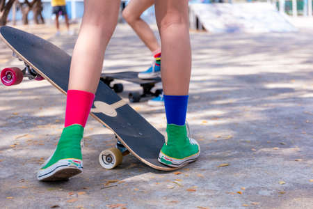 Close-up Asian girl surf skate or skateboard outdoors on beautiful morning. Happy young girl play surf skate at ramp park on morning time. Close up Asian women leg wear sneaker play surf skate on public park. Sport concept