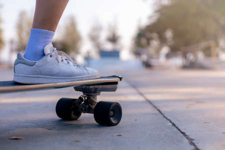 Close-up Asian women surf skate or skateboard outdoors on beautiful morning. Happy young women play surf skate at ramp park on morning time. Close up Asian women leg wear sneaker play surf skate on public park. Sport concept