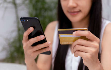 Young woman holding credit card and using laptop computer. Women working at home. Online shopping, e-commerce, internet banking, spending money, working from home concept. Technology shopping online concept. Banco de Imagens