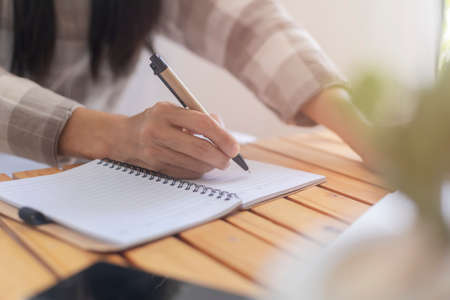 Close up hand of business woman use pen writing document paper. Female hand close up writing with a blue pen on a white sheet. Woman writes information on a piece of paper. Archivio Fotografico