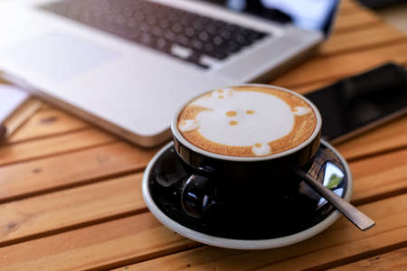 Top view hot coffee cup with blur laptop smarthphone and note book on wood table. office desk with smart phone laptop and coffee cup. Business concept. Process with vintage style
