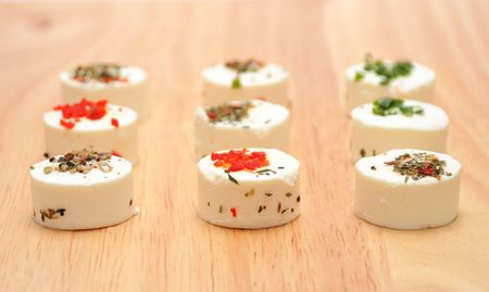 Goat cheese with herbs and toothpicks on wood board Archivio Fotografico