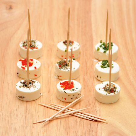 Goat cheese with herbs and toothpicks on wood board Stock Photo - 4690980