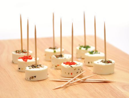 toothpick: Goat cheese with herbs and toothpicks on wood board Stock Photo