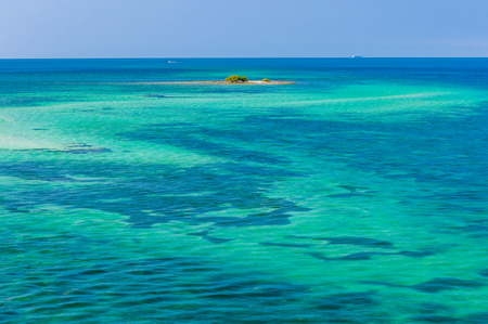 Travel background: water of tropical sea and tiny coral reef