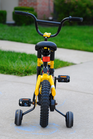 static bike: Small bicycle standing in front of house