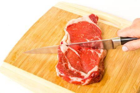 Cut ribeye steak on wooden board
