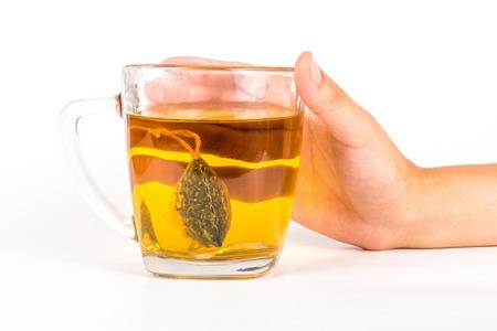 green and black: Hand holding glass mug of herbal tea