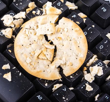 comiendo pan: galleta rota dará a su teclado roto demasiado Foto de archivo