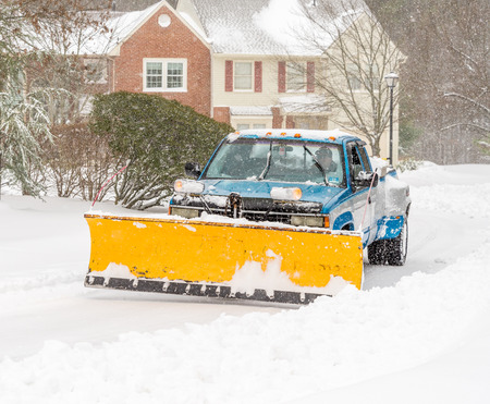 blanketed: Snow plough truck clearing road after whiteout winter snowstorm blizzard for vehicle access