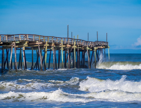 Old wood fishing pier at the sandy beach Stock Photo