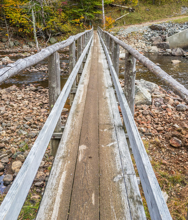 Old wood pedestrian bridge over the mountain river