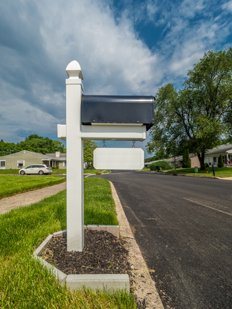 Residential mailbox at the quiet street with bright blue sky on background