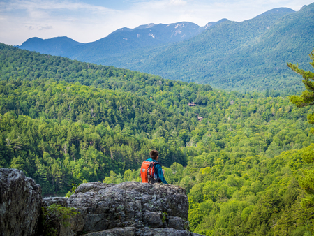 Boy sits at the edge of the cliff on top of Roaring Fall in Adirondack Mountains Banque d'images
