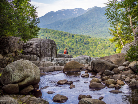 Boy sits at the edge of the cliff on top of Roaring Fall in Adirondack Mountains