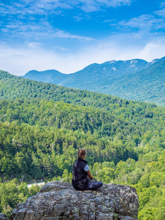 Girl sits in yoga pose at the edge of the cliff Stock Photo