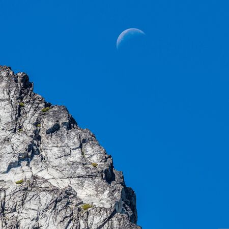 Crescent moon over the rocky peak in the blue morning sky