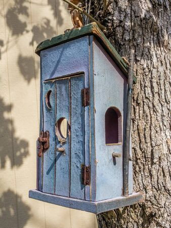 Rustic bird house hanging on the tree