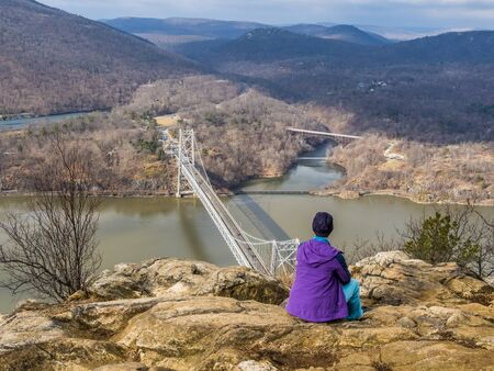 Hiker is sitting on the cliff of Anthony's Nose over the Hudson River in Upstate New York Stock Photo