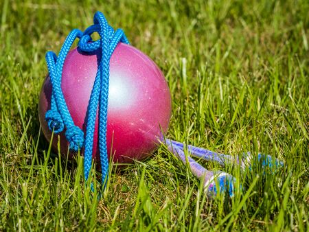 Rhythmic Gymnastics equipment in the grass during outdoor practice  Фото со стока