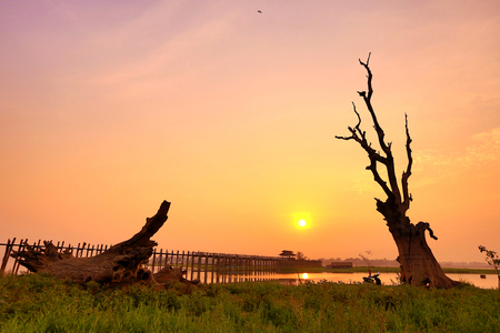 teck: wooden teck bridge with reflections at susnet in Amarapura, Myanmar (Burma) Stock Photo