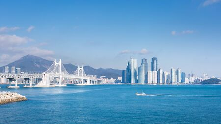 busan city and Gwangan bridge and fisherman's boats, Haeundae, Busan,Korea.