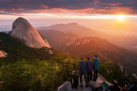SEOUL, KOREA - June 28, 2015: Photographer is taking a photo of the sunrise in the morning on  Bukhansan mountains , Seoul, South Korea.