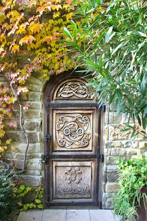 "Beautiful carved wooden door in a stone wall overgrown with plants. Russia, Kabardinka "" Old Park"""