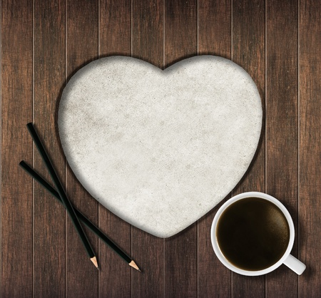 Wooden planks heart shape with pencil and coffee photo