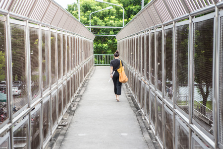 Woman walking on the pedestrian overpass on a tree background