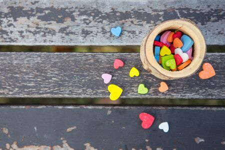 many little heart colorful in a wooden cup on an old wooden table with sunlight and natural background