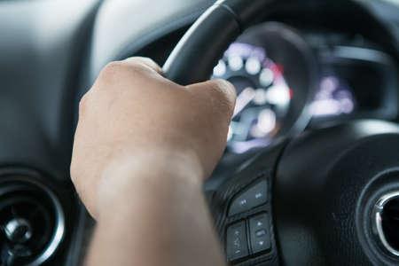 Men's hand holding the steering wheel