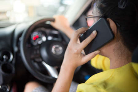 Blurred of Women talk mobile phone while driving