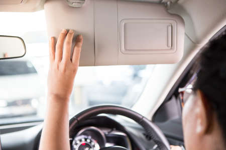 Woman hand holds the sun visor in the car