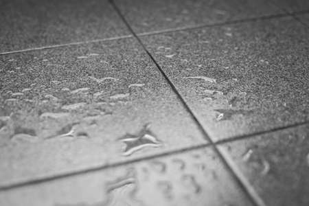 Black and white Selective focus of Water drops on the tile floor texture background